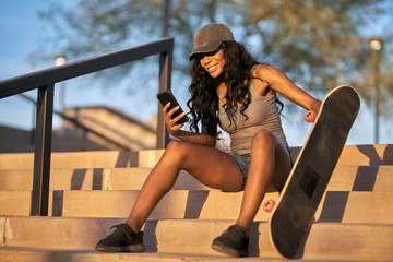 smiling african american woman in skatepark with skateboard using smartphone