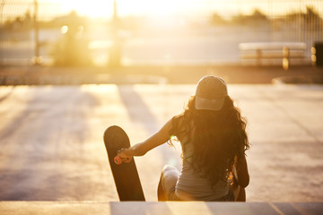 Rear view of young woman sitting with skateboard on steps at park during sunset