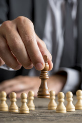 Businessman playing chess moving black king piece lifting it up in his fingers