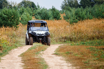 Young people on quad bikes on a countryside trail.