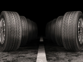 Car tires standing on the road on black background.