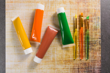Colours of the nature - mix of green, yellow and brown - home or office interieur design concept, tubes with acrylic paint and green brush