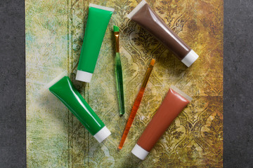 Colours of the nature - mix of green and brown - home or office interior design concept, tubes with acrylic paint and green brush