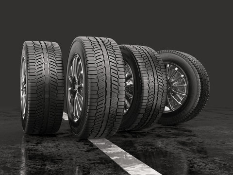 Four car tires rolling on a road on a gray background.