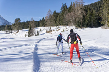 Two cross-country Skiers runs on groomed ski track in sunny winter day. Winter mountain landscape: Tirol, Alps, Austria.