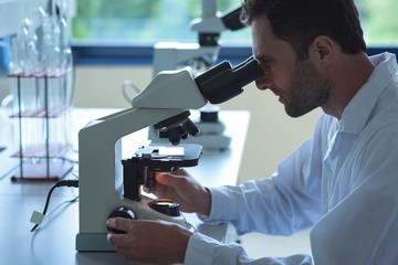 University student doing experiment on microscope in laboratory
