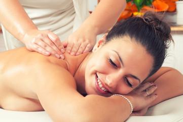 Happy woman enjoying professional back massage in modern beauty spa