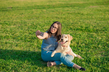 Cheerful cute young woman taking selfie with golden retriever dog on green meadow. beautiful girl and her dog make self-portrait themselves by phone