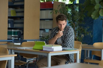 Young male university student studying at desk