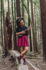 Stylish girl with ukulele in woods