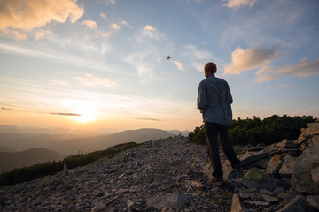 Traveler stands in the mountains and controls the drone