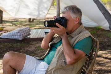 Man photographing outside tent