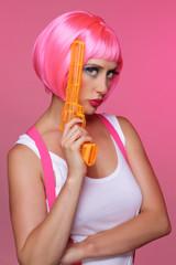 femme avec perruque rose et revolver en plastique
