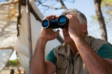 Man looking through binocular Fotoväggar