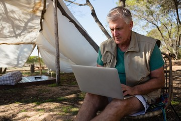 Man using laptop at campsite