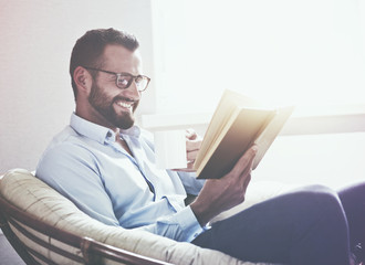 smiling handsome man reading book drinking coffee or tea