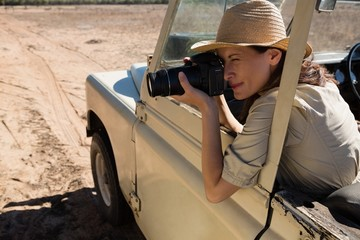 Woman photographing in off road vehicle