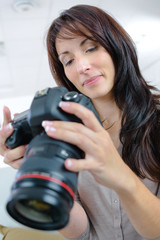 female photographer holding a professional camera