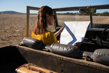 Woman reading map while sitting in vehicle