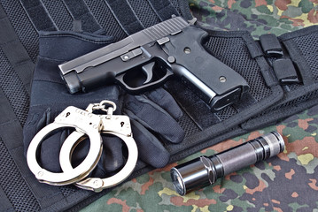 Handgun with handcuffs, gloves and flashlight on tactical vest and camouflage clothing