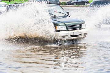 Splash by car as it goes through flood water after heavy rains of Harvey hurricane storm in Houston, Texas, US. Flooded city road with big puddle of water spray from the wheels of SUV car roaring by.