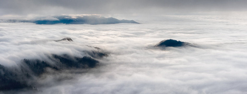 Beautiful scenic autumn evening mountain landscape of Caucasus mountains rising above shroud of heavy low scattered clouds. Wide angle panorama