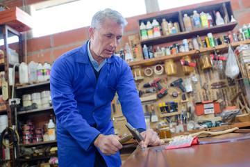 senior carpenter restoring old furniture