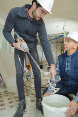 construction worker telling worker how to mix cement indoors