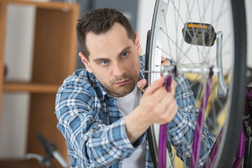 young bicycle technician adjusting rays on a wheel