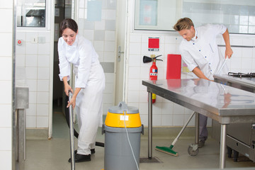 kitchen aids are cleaning the restaurant kitchen