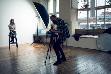 Side view of man photographing fashion model
