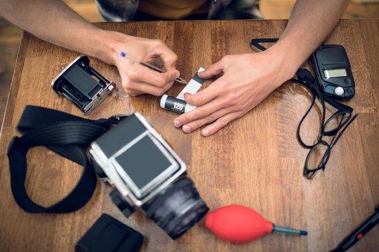 Photographer writing on film reel