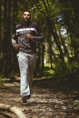 Full length of young male running in forest