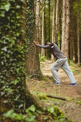Side view of man exercising in forest