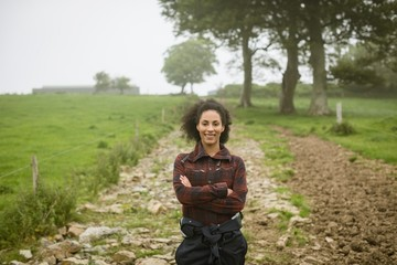 Female farmer standing with arms crossed in field