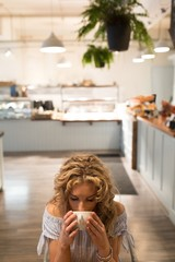 High angle view of young woman drinking coffee