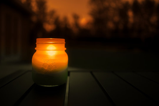 A close up of a lit candle in a mason jar outdoors in the evening