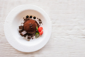 Chocolate fondant with decoration from strawberry and mint on wooden table. Delicious dessert serving in restaurant, top view with free space