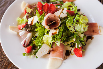 Salad lettuce with parma ham, blue cheese and strawberry serving in restaurant on wooden table. Gourmet cuisine close up picture