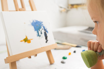 Thoughtful little painter in art studio. Early childhood education, creative painting process. Interesting hobby for children, artistic concept