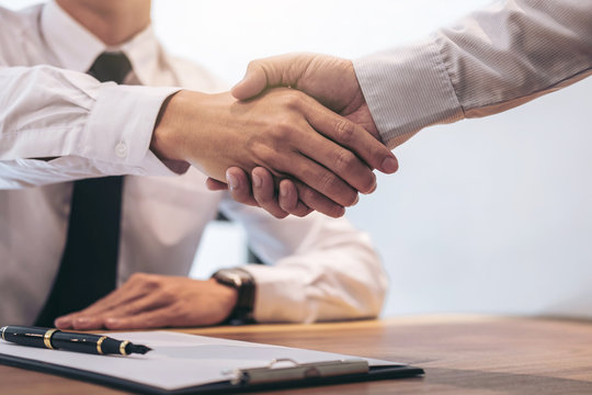 Estate broker agent and customer shaking hands after signing contract documents for realty purchase mortgage loan approval