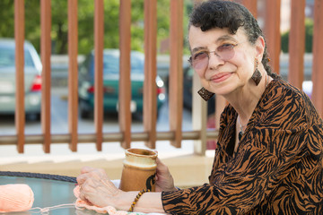 Closeup side view profile portrait, grandmother enjoying cup of drink, isolated outdoors background