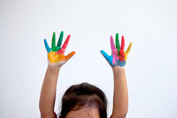 Hands painted of little child girl in colorful paint on white background