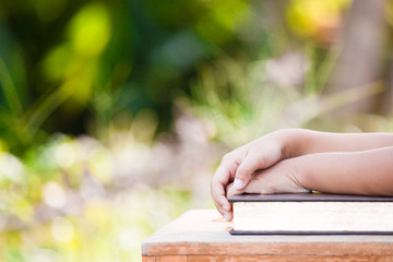 Little child girl hands folded on book in outside in nature background