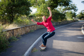 stylish skater in red shirt and blue jeans ride downhill on longboard, summer active picture