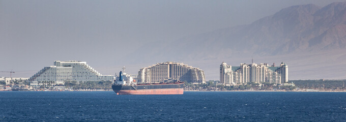 Cityscape of resorts in Port of Eilat, Israel in the middle east. Tanker and merchant ships are a common site in the foreground. / Eilat, Israel Cityscape