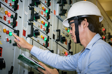 industrial technician check current status in control panel of power plant.