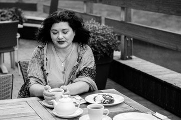 Mature woman in bright scarf, size plus american or European appearance sitting in a restaurant drinks coffee at autumn day. Lady with excess weight, stylishly dressed in cafe waiting for a friend
