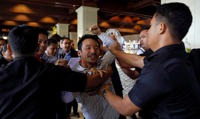 Security guards scuffle with anti-mining protesters at the lobby of a hotel where the Philippines annual mining conference is held in Pasay