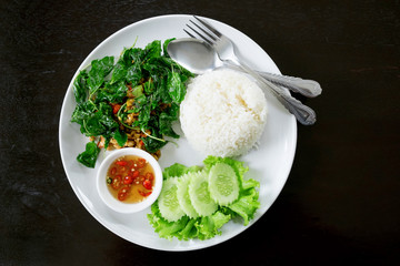 Pork chop with crispy basil dish, Yummy meal on dark wood table.